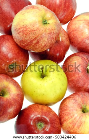 one ripe yellow apple with red apples