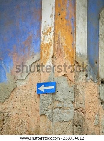 One way street sign in Havana, Cuba on a crumbling wall - stock photo