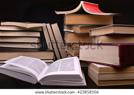 open book and pile of books against a dark background - stock photo
