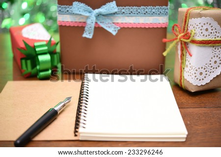 open notebook and gift box on green background.  - stock photo