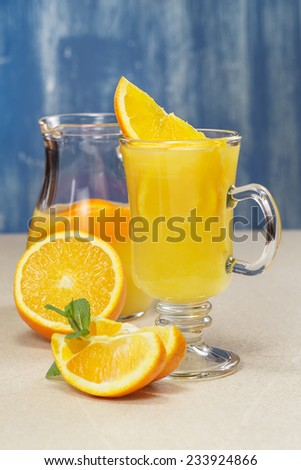 Orange juice.  Orange juice and fresh oranges over rustic background. A macro photograph, shallow depth of field - stock photo
