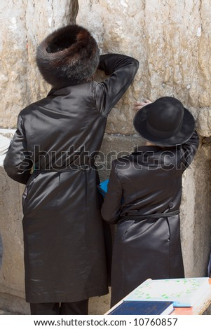 Orthodox father and son pray at the Western Wall in Jerusalem. - stock photo