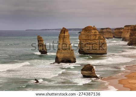 6 out of famous 12 apostles at Great Ocean Road national park in Victoria, Australia. Close-up view at sunrise sandstone rocks standing out of surfing waves at the edge of Southern ocean - stock photo