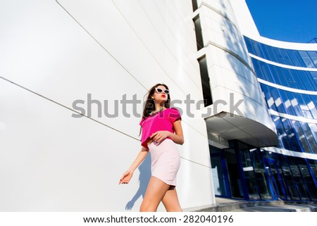 Outdoor Fashion portrait of glamour bright successful business in pink top and skirt with perfect long legs walking against modern urban background.  - stock photo