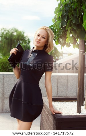 outdoor portrait of young stylish woman standing near trees - stock photo