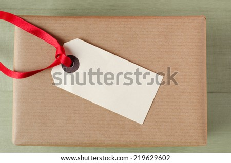 Overhead shot of a wrapped brown paper gift package on a green table. Topped with a parcel tag and red ribbon.  The blank label faces upwards to provide copy space for a message.   - stock photo