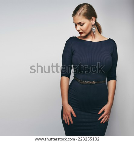 Oversized and curvy female model on grey background. - stock photo