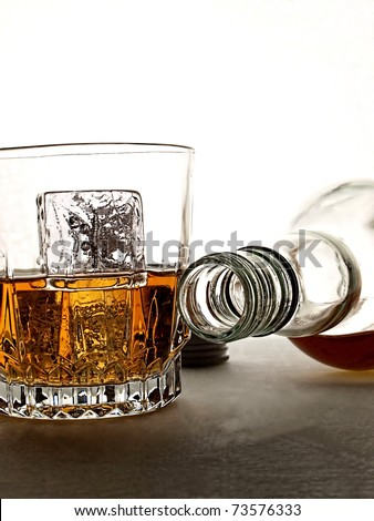 Overturned whiskey bottle and glass in front of white  background. - stock photo