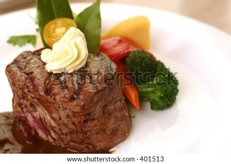 8 oz tenderloin steak dinner with an accompaniment of mashed potatoes, tomatoes, broccoli and butter. shallow DOF. - stock photo