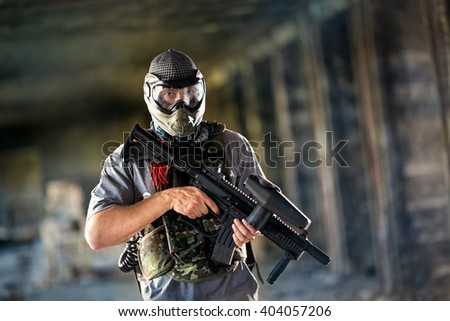 Paintball player with protective mask and gun  - stock photo
