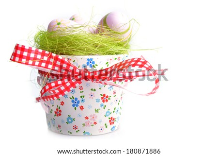 painted easter eggs on green in decorative bowl