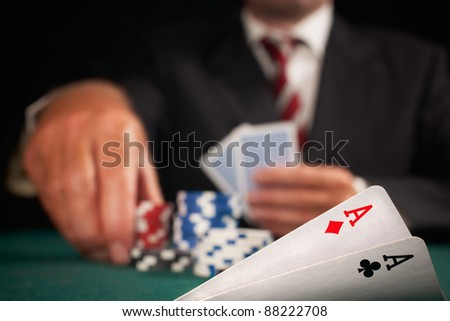 pair of aces and poker player gambling casino chips on green felt background selective focus - stock photo