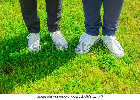 2 pairs of legs with white sneakers and jeans on the background of grass. The concept of a young couple