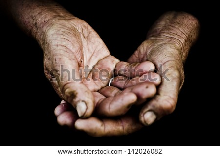 palms of  old man on a black background. - stock photo