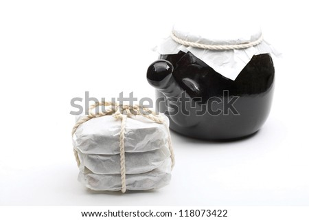 3 paper bags of ingredients wrapped in a rope next to the black kettle