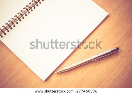 paper notebook and pen on a table with filter effect retro vintage style - stock photo