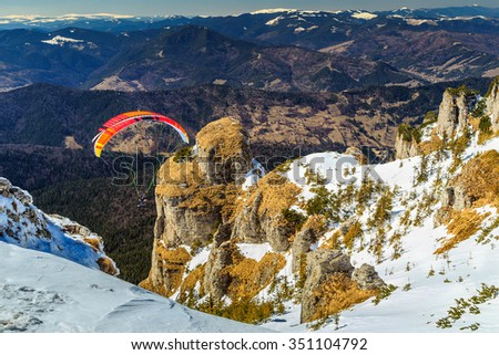 Paraglider flying over snowy peaks in winter day,Ceahlau mountains,Carpathians,Transylvania,Romania,Europe - stock photo