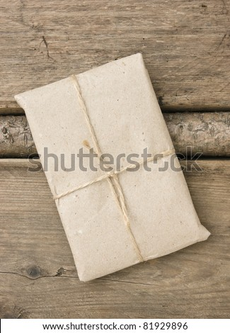 parcel wrapped with brown kraft paper and tied with twine - stock photo