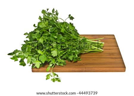 Parsley green leaf on wooden cutting board. - stock photo