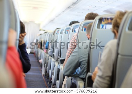 Passengers are sitting and sleeping on an airplane. They get stuck in their seat in a long and boring flight.  - stock photo