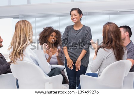 Patient has a breakthrough in group therapy and everyone is clapping her - stock photo