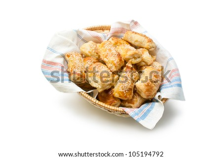 Patties. Freshly baked patties from puff pastry filled with cheese sprinkled with sesame seeds arranged in a wicker basket  isolated on white background. - stock photo