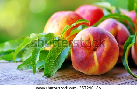 peaches and leaves on table - stock photo