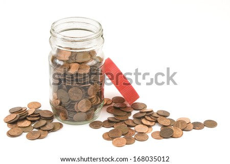 Pennies and jar on white background.