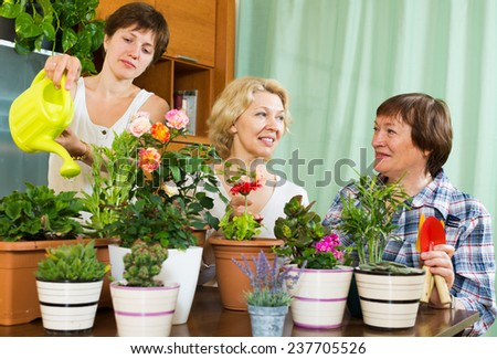 pensioners  and girl  caring for decorative plants