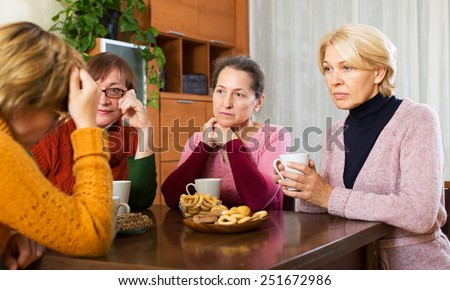 pensioners listening to sad story of their friend at table  indoor - stock photo