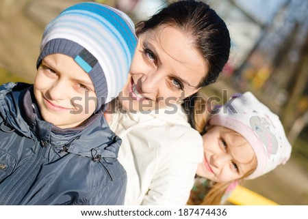 3 people beautiful young mother with two children, son and daughter having fun happy smiling & looking at camera, closeup portrait on spring or autumn outdoors background   - stock photo