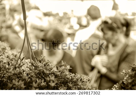 People buying flowers at Columbia Road Flower Market. London, UK. Selective focus. Blurred People. Aged photo. Sepia. - stock photo