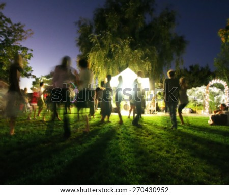 people mingling at a free concert by local musicians long exposure at night  - stock photo