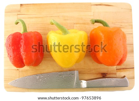 peppers on board with knife isolated on white - stock photo