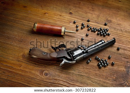 percussion pistol revolver on the wooden table still life with powder box and lead - stock photo