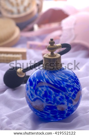 Perfume spray bottle on a fabric background.  - stock photo