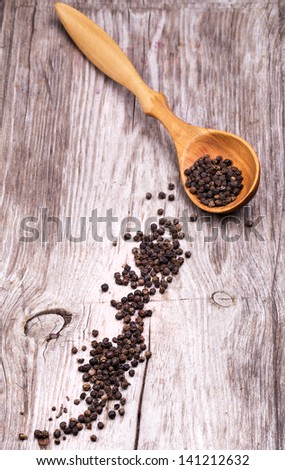 photo of Spoon with pepper on vintage wooden table with black background - stock photo