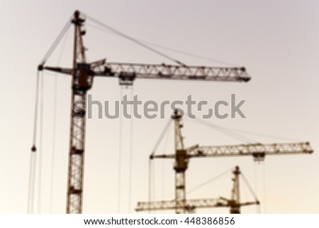 photographed close-up construction cranes during construction of a new multi-storey residential building, multi-colored sky during sunset, defocus