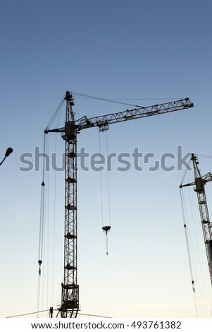 photographed close-up  cranes during construction of a new multi-storey residential building