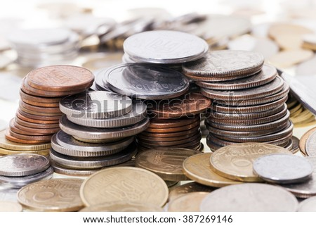 photographed close-up metal coins stacked in a pile, the background of the coins