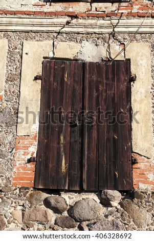 photographed close-up of old building with boarded and the doors and windows closed - stock photo