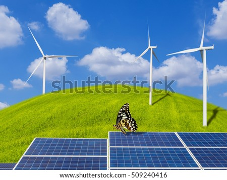 photovoltaics solar panels and butterfly with wind turbines generating electricity on grass hill and blue sky with clouds.Ecology green nature concept.
