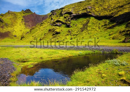 Picturesque basalt hills overgrown green grass and moss. On bottom of canyon many streams flow. Canyon Pakgil in Iceland - stock photo
