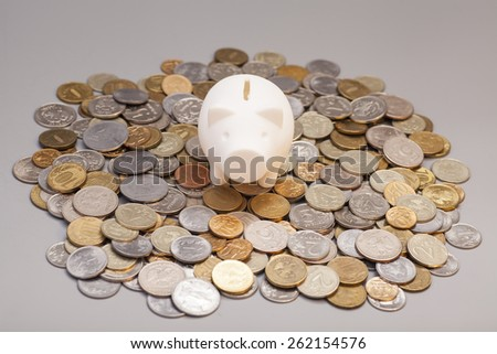 piggy bank on coins isolated on gray