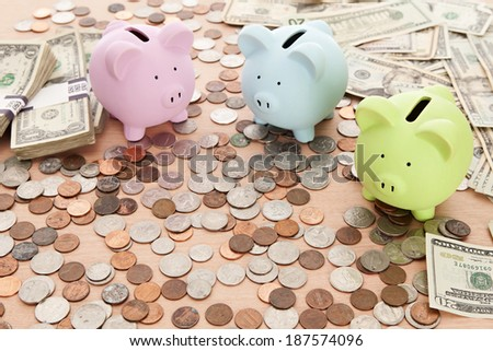 3 Piggy banks, some loose change and dollar bills on a desk.  Main focus on green bank.
