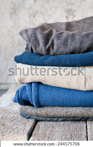 Pile of clothes on a wooden background - stock photo