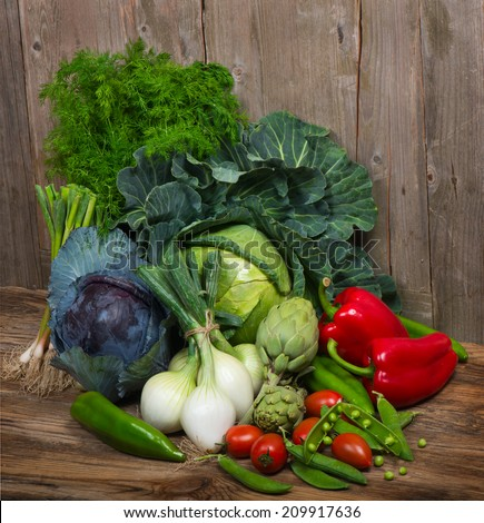 Pile of fresh vegetables and herbs on wooden  background - stock photo