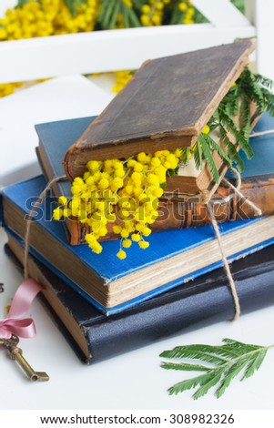 pile of vintage old books  on white table with mimosa flowers - stock photo