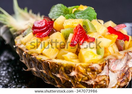 Pineapple dessert stuffed with tropical fruits - stock photo