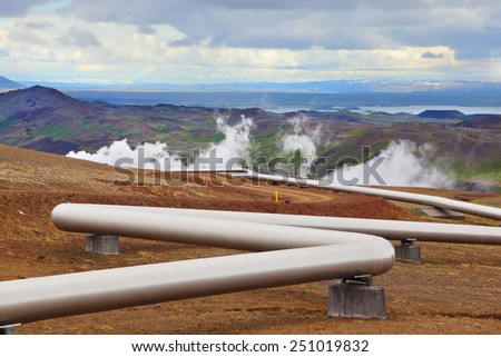 Pipeline to transport hot water. Summer Iceland. Krafla Lake neighborhood. Steam rises above the hot ground - stock photo